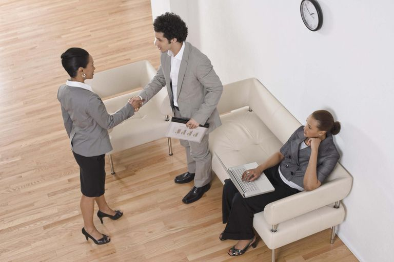 Business people shaking hands in waiting area