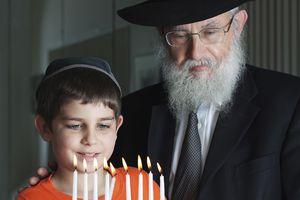 Two Jewish people celebrate Hanukkah by lighting the menorah