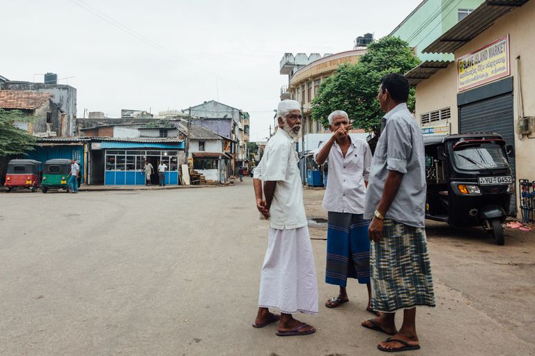 Muslim men in sarongs have a chat in Slave Island