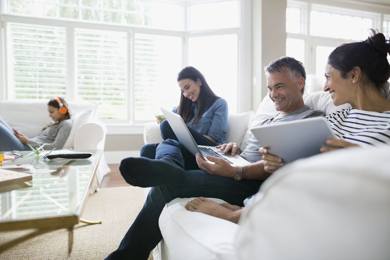 Family using wireless technology on living room sofa