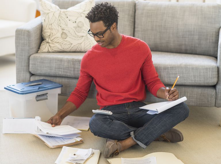 Man sitting on floor in living room and calculating bills