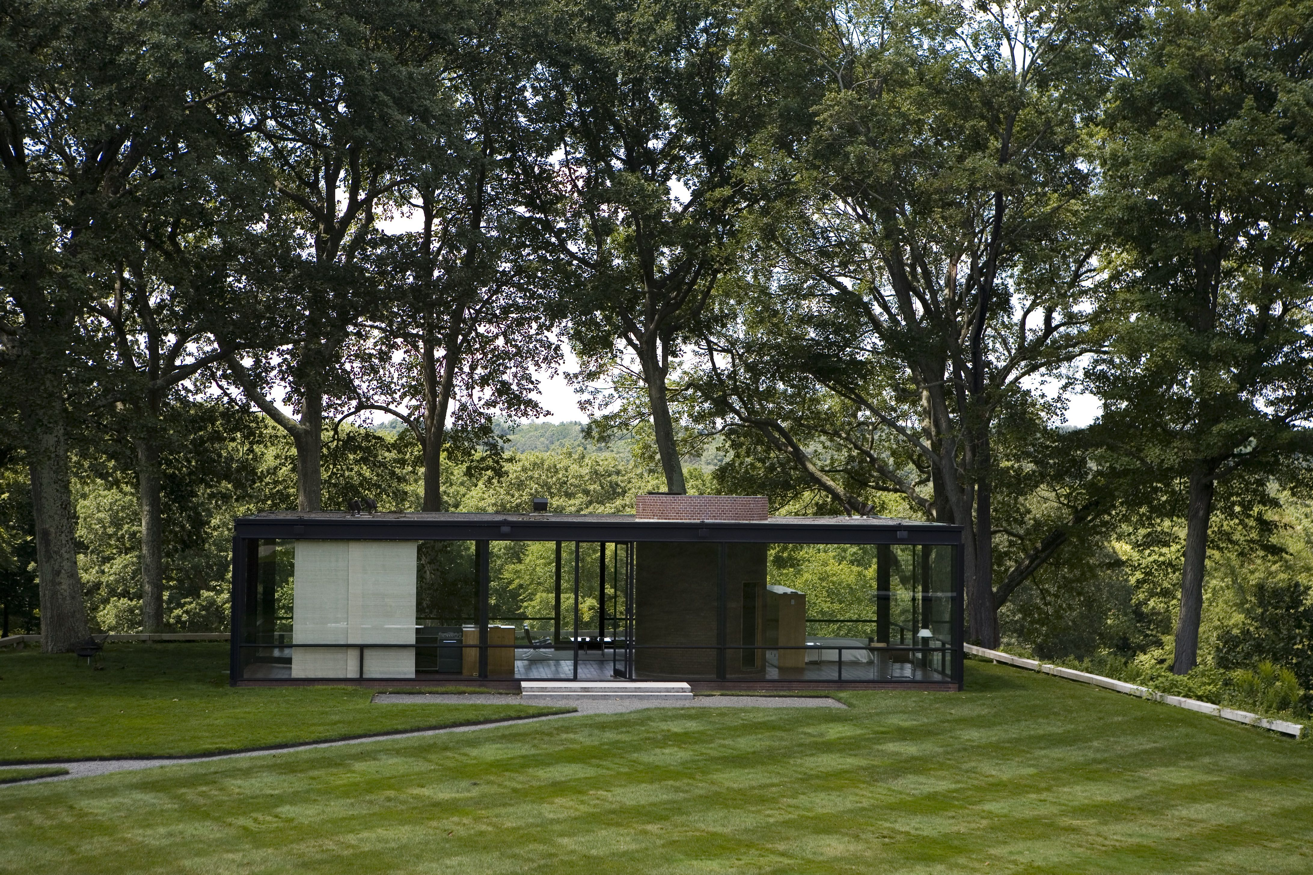 distant view of glass box house amidst woodland
