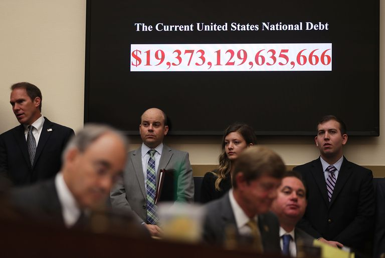 HUD Secretary Julian Castro standing in front of a chart showing the US national debt