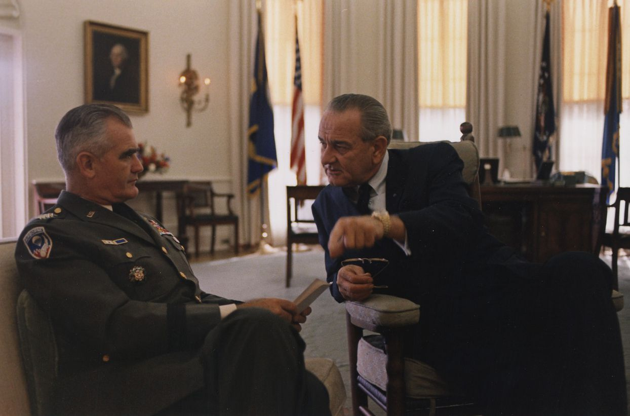 General William Westmoreland, in US Army uniform and seated speaks with President Lyndon B. Johnson in the Oval Office.