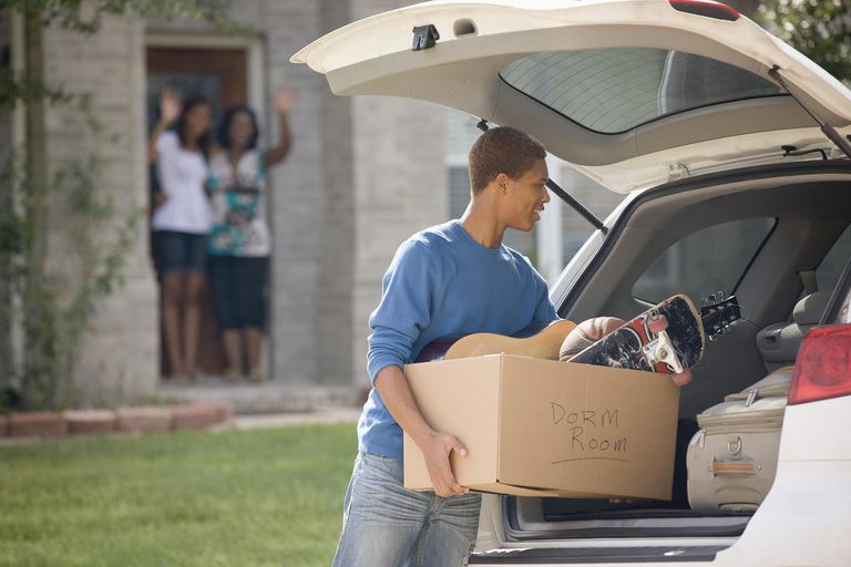 Man loading car for college, while family waves goodbye.