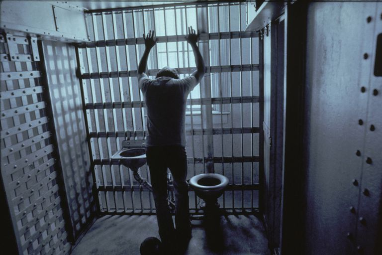 Man in jail cell with arms on bars