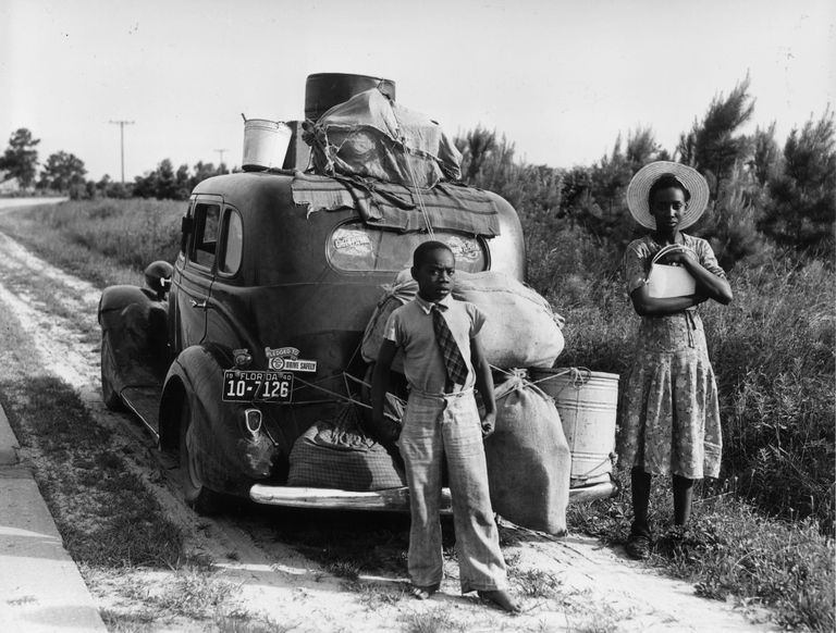 black woman and young boy standing in front of packed car
