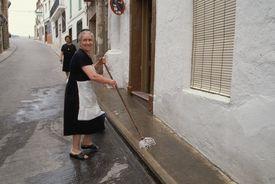 Woman Cleaning Sidewalk in Spain