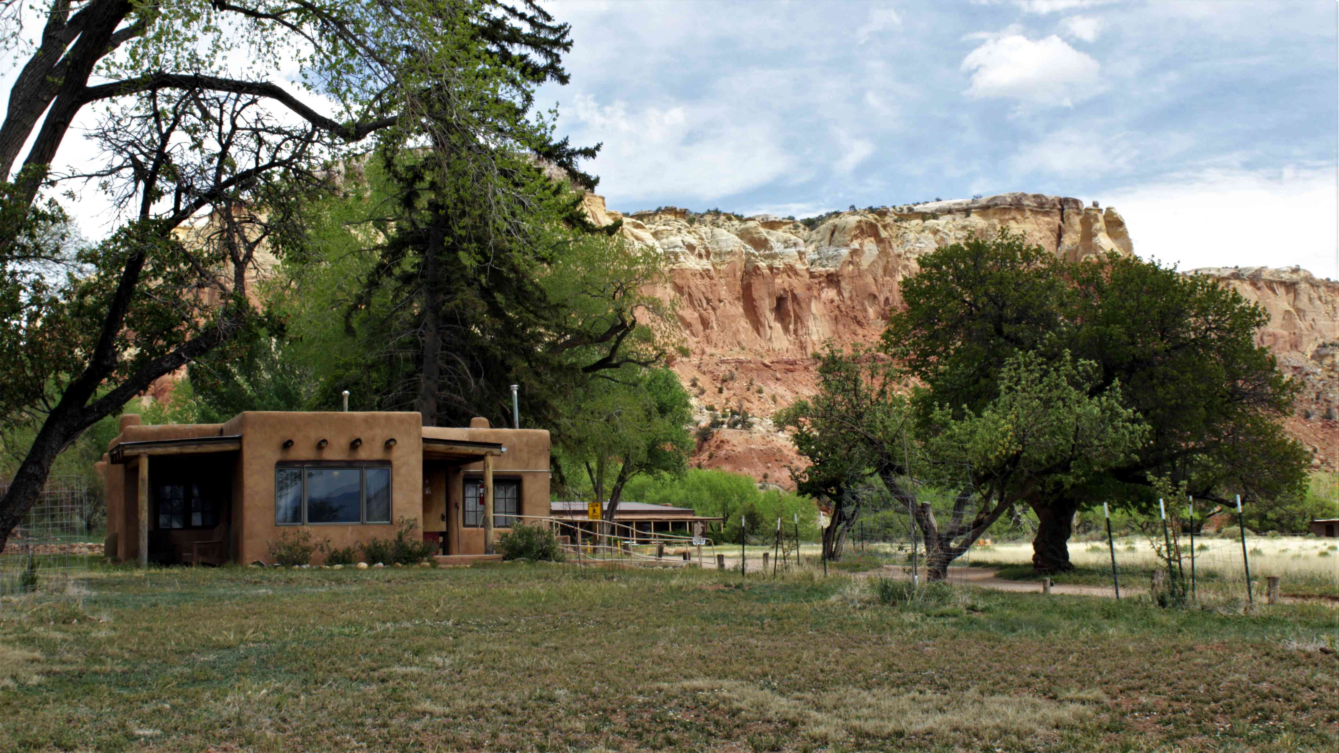 Image of Georgia O'Keeffe's Ghost Ranch in Abiquiu, New Mexico surrounded by trees and desert landscape