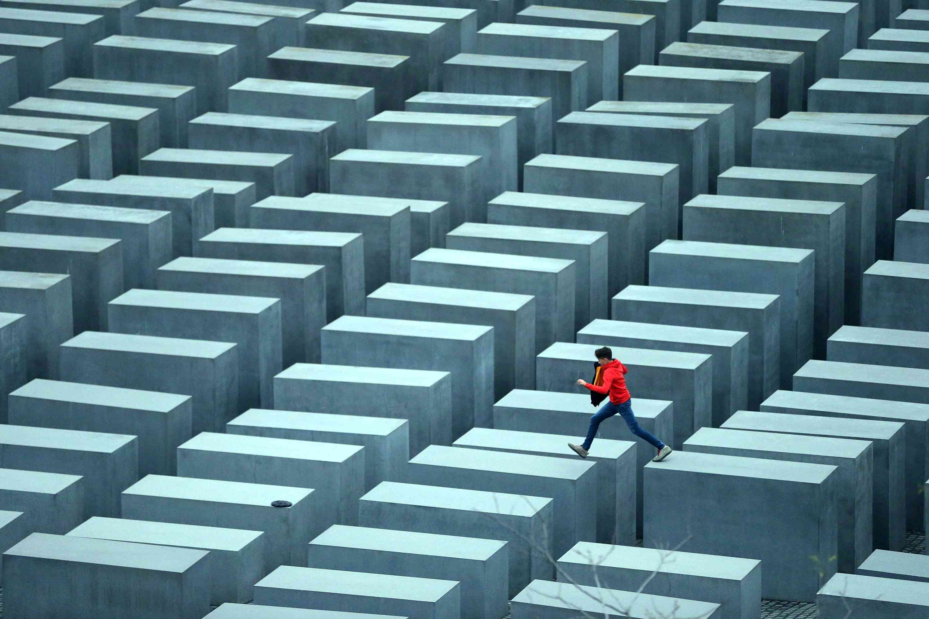 A boy in a red jacket hops from one to another of the 2,711 stellae, concrete tombs that together make a Memorial to the Murdered Jews of Europe
