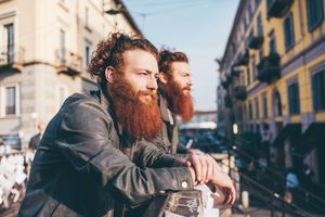 Young male hipster twins looking out from city footbridge