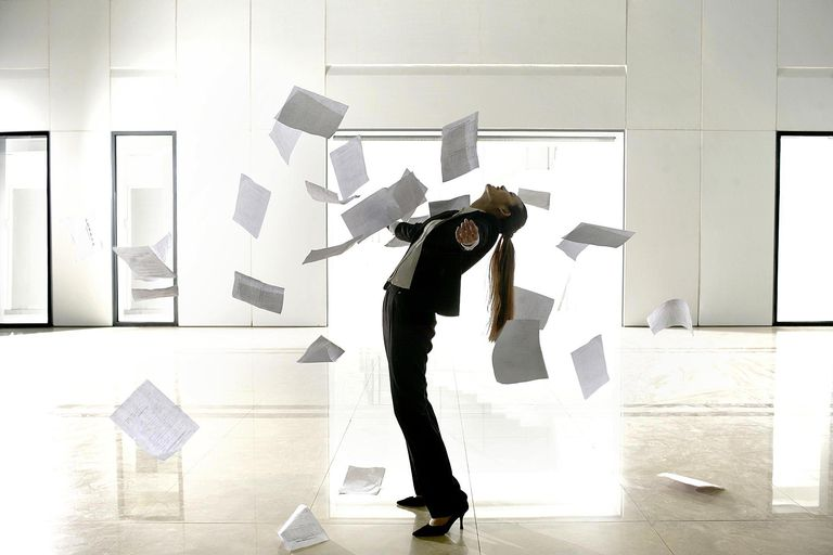 Business woman throwing papers in air