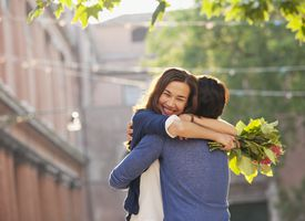 Woman with flowers hugging man
