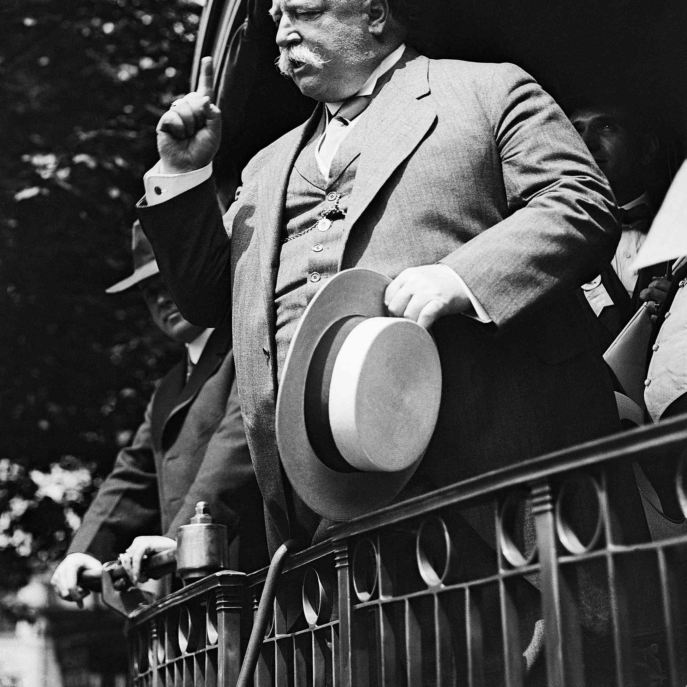 Black and white photo of president-to-be William Howard Taft making a campaign speech from a train platform.