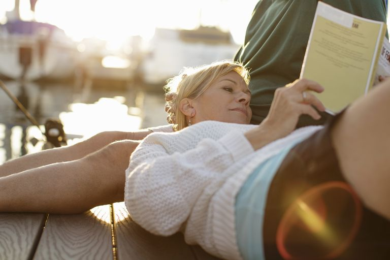 Mature woman lying on marina pier reading book, Redondo Beach, California, USA