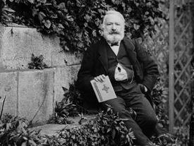 Victor Hugo sitting on a stoop among leaves