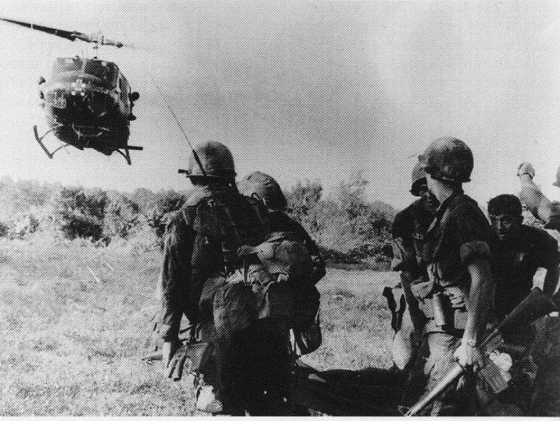 UH-1 Huey helicopter landing near a group of soldiers.