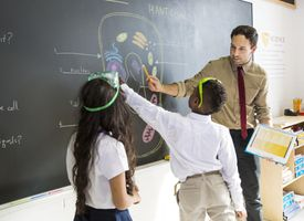Science teacher explaining a diagram to students.