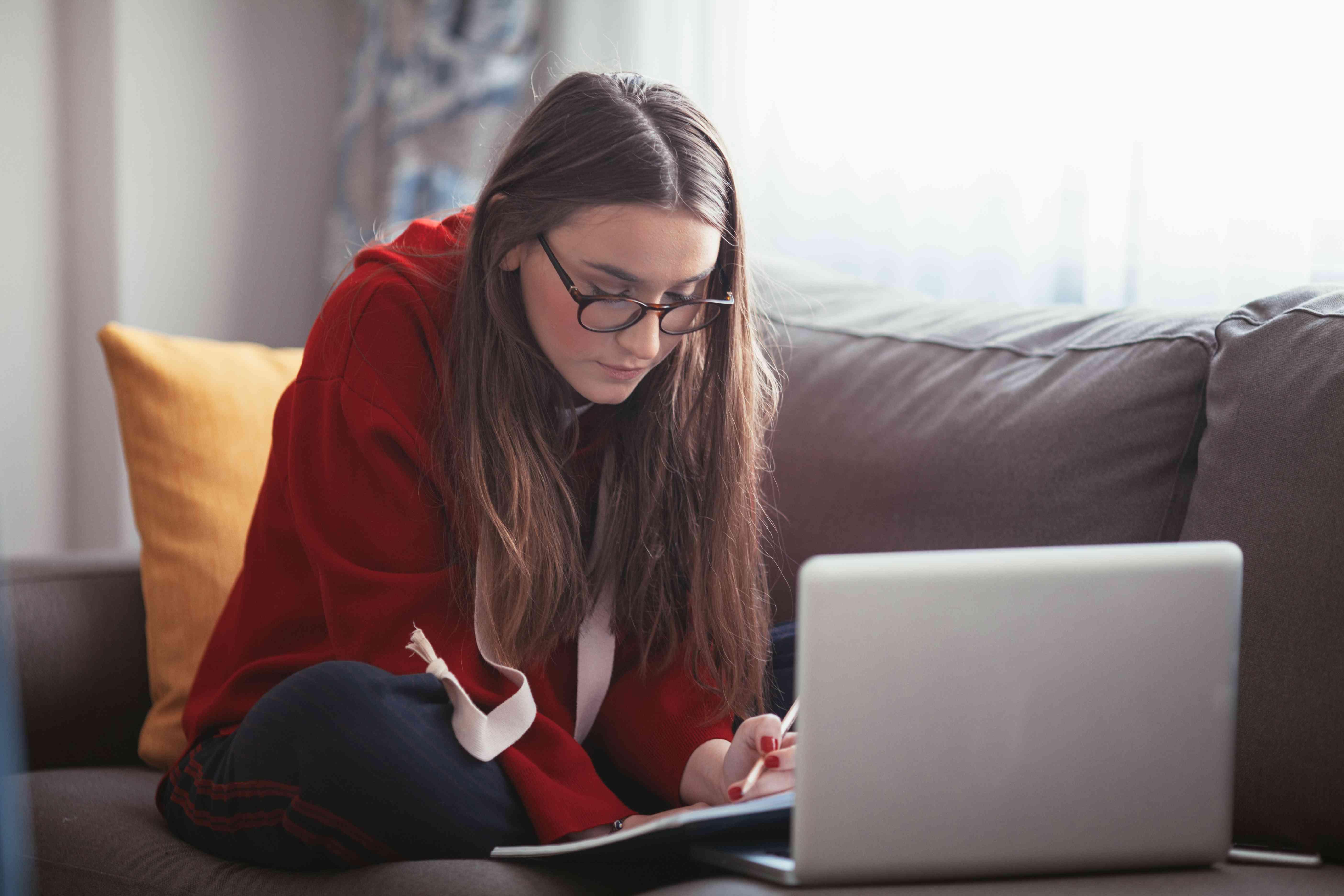 Woman studying on sofa
