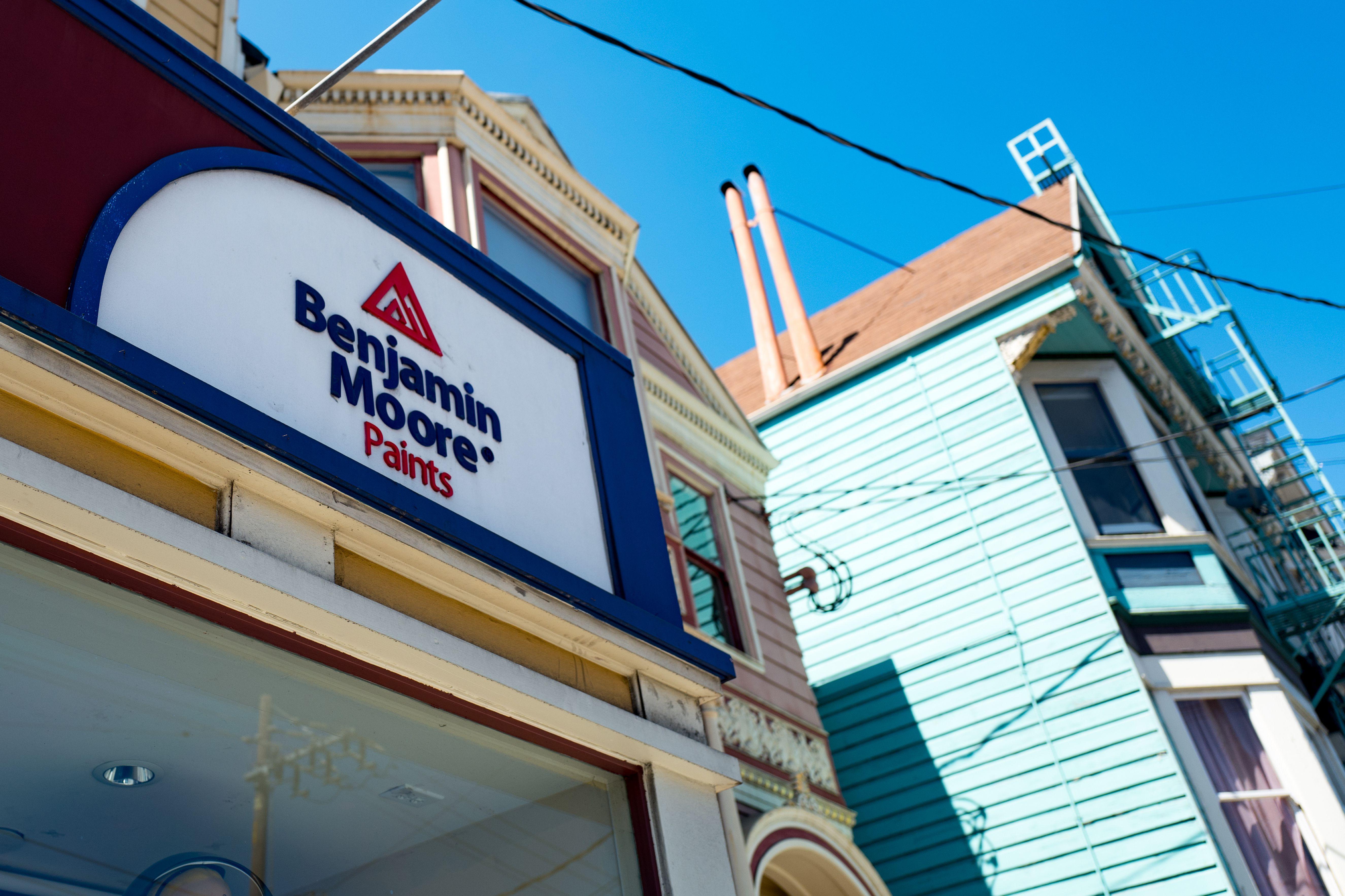 Beschilderung für Benjamin Moore Farbenladen, mit hell gestrichenem Haus im viktorianischen Stil im Hintergrund