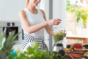 woman using blender to make smoothie