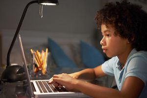 Young Boy Studying At Desk In Bedroom Youn...