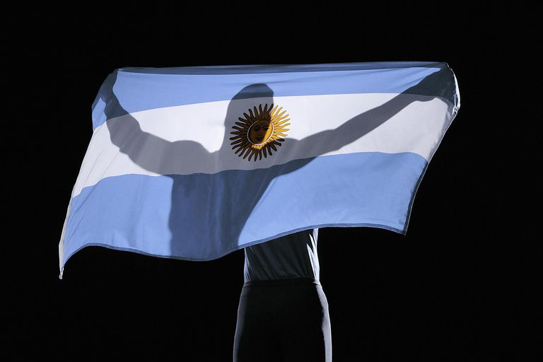 Silhouette of person holding flag of Argentina on black background