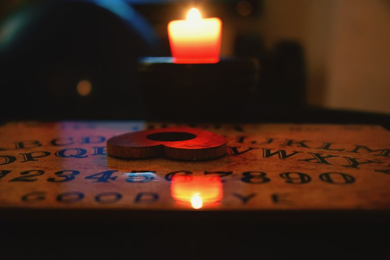 Heart shaped planchette on Ouija board by a candle in a darkroom
