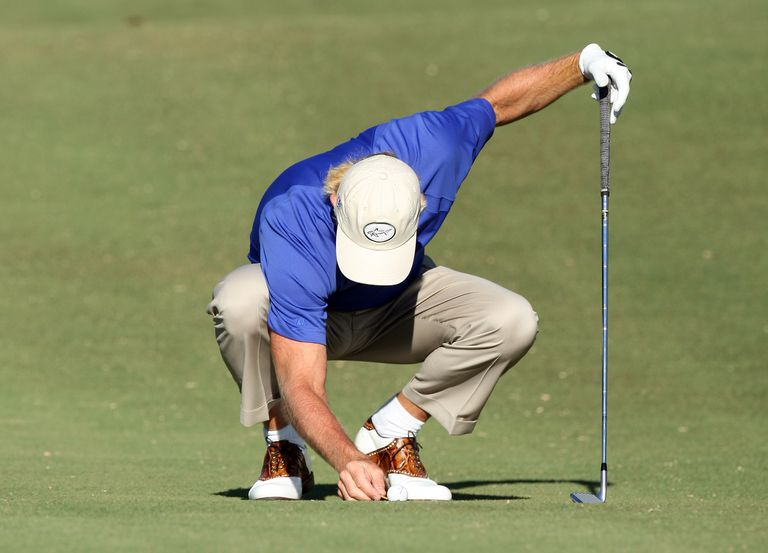 Golfer Greg Norman removes a loose impediment from behind his golf ball in the fairway.