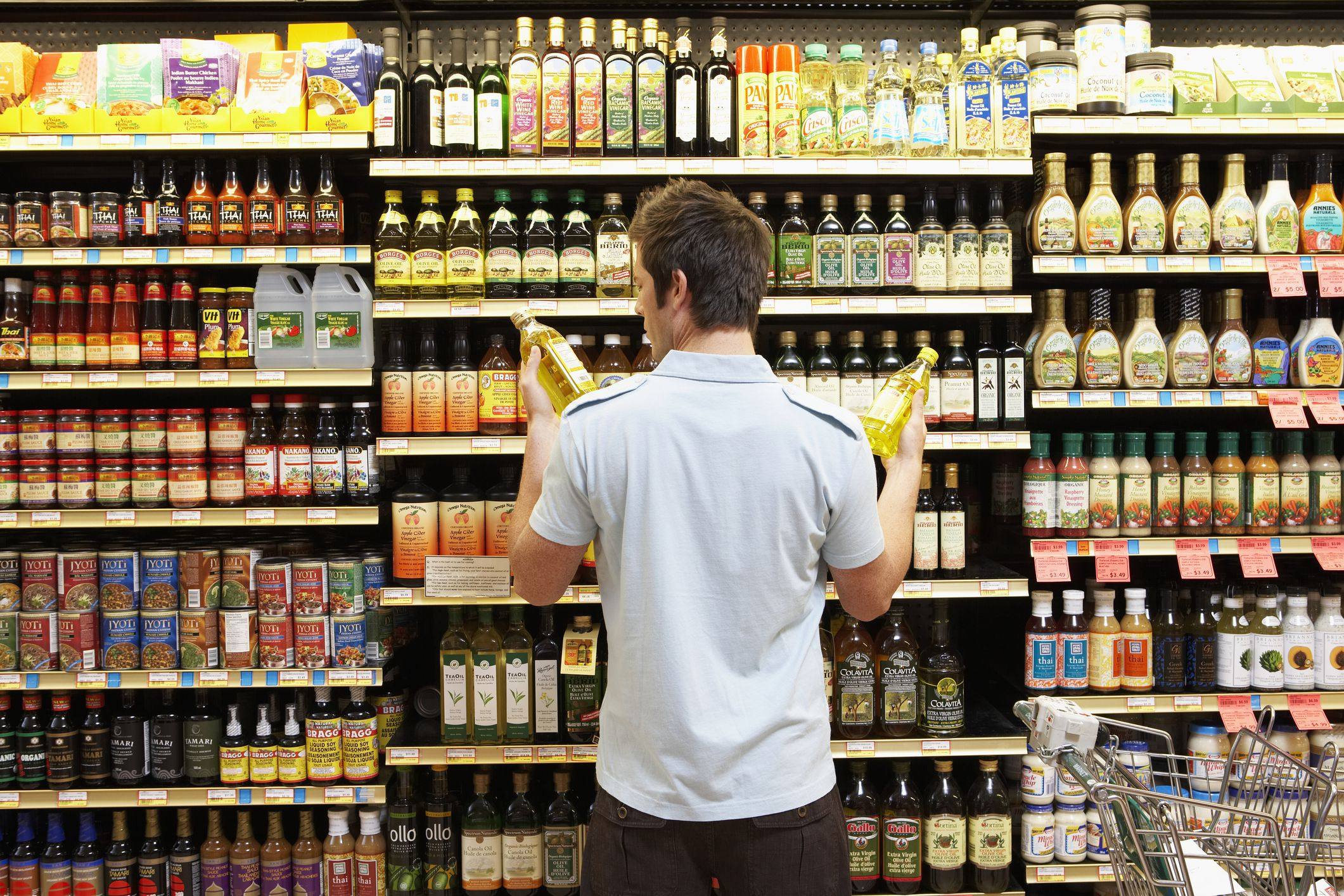 A man looking at oils in grocery store aisle