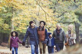 Multi-generational family walking in autumn woods