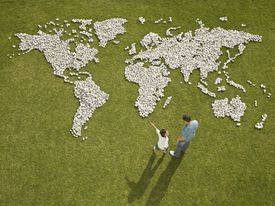 Father and son looking at a world map made with rocks on the grass.