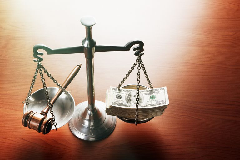 Scales of Justice with stacks of dollars