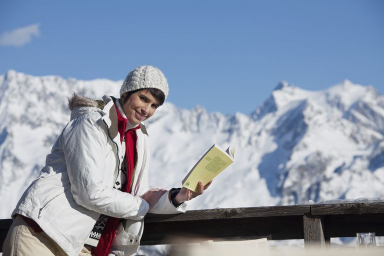 Young woman reading a book, enjoying winter sun, mountains in background