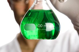 Woman holding glass containing green liquid