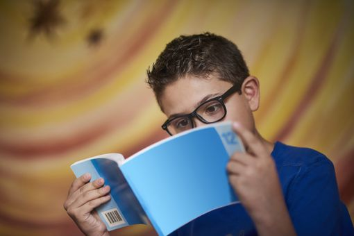Middle school boy reading a book