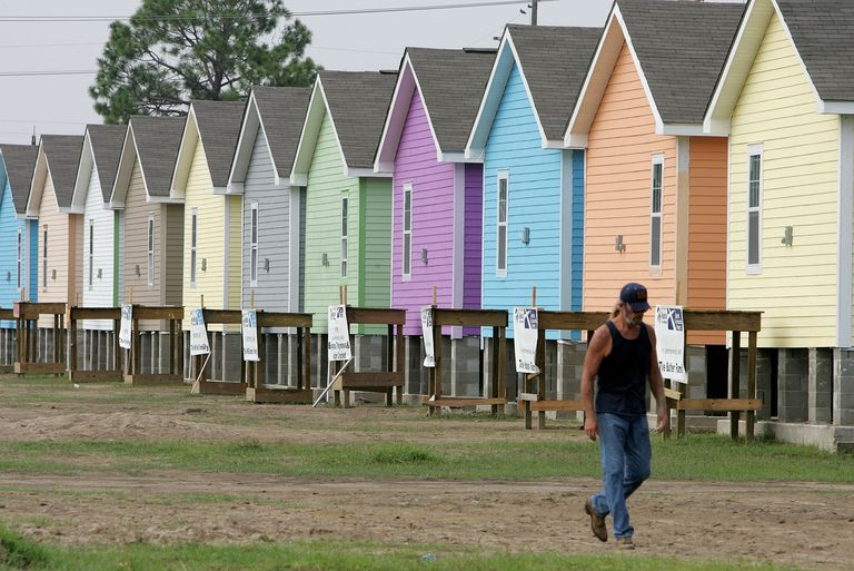 A volunteer construction worker with Habitat for Humanity walks in front of a row of newly constructed homes August 23, 2006 in Upper Ninth Ward of New Orleans, Louisianna.