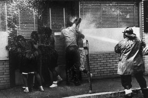Firemen bear in on a group of black Americans who sought shelter in a doorway in Birmingham, Alabama, 3rd May 1963.