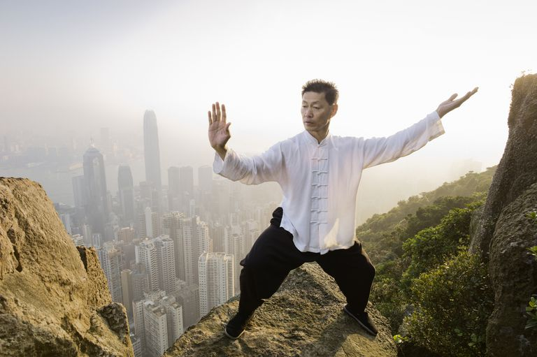 Man on top of mountain about cityscape doing a slow-moving Martial Arts