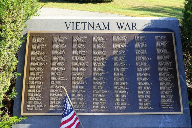 Vietnam War memorial showing names of the dead with an American flag in the sunlight.