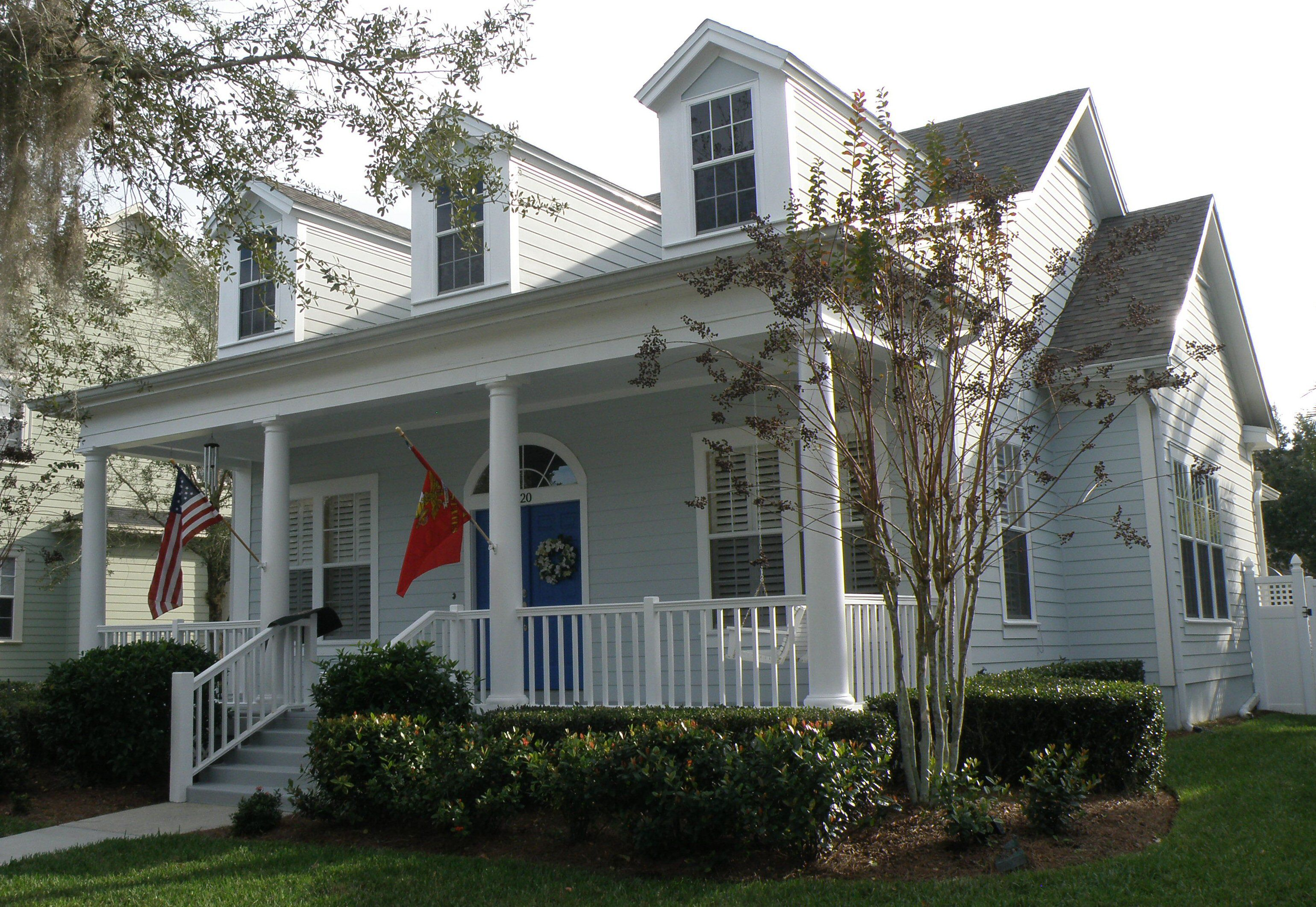 Three dormers and front porch on neighborhood house