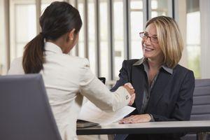 Dos mujeres saludándose con la mano antes de comenzar una entrevista