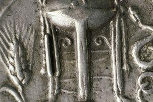 A silver coin depicting the Delphic tripod.
