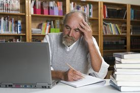 Man contemplating information to include in his book
