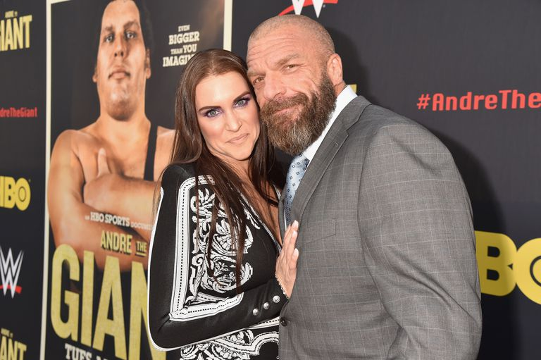 Triple H and Stephanie McMahon posing in front of documentary poster.