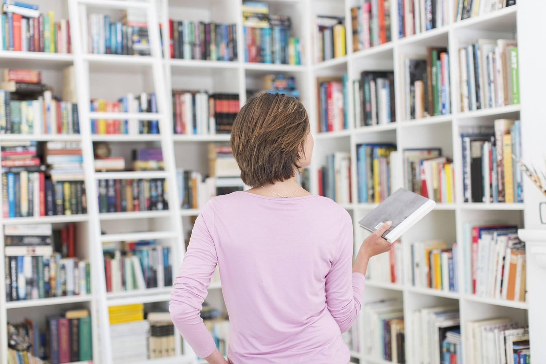 Frau, die Buch aus Bibliothek auswählt