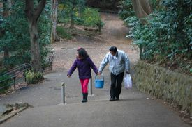 Two people carrying a bucket up a hill