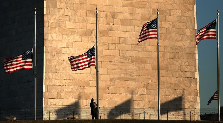 American flags being lowered to half staff at base of Washington Monument
