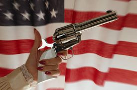 Woman holding antique cavalry pistol, close-up, USA flag in background