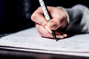 A girl's hand holding a pen while writing in a notebook